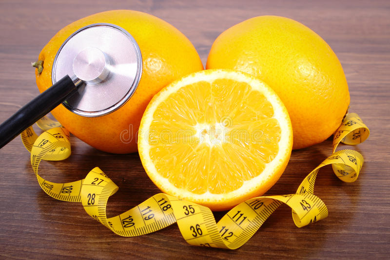 Stethoscoop, verse sinaasappel en centimeter, gezonde levensstijlen en voeding royalty-vrije stock foto