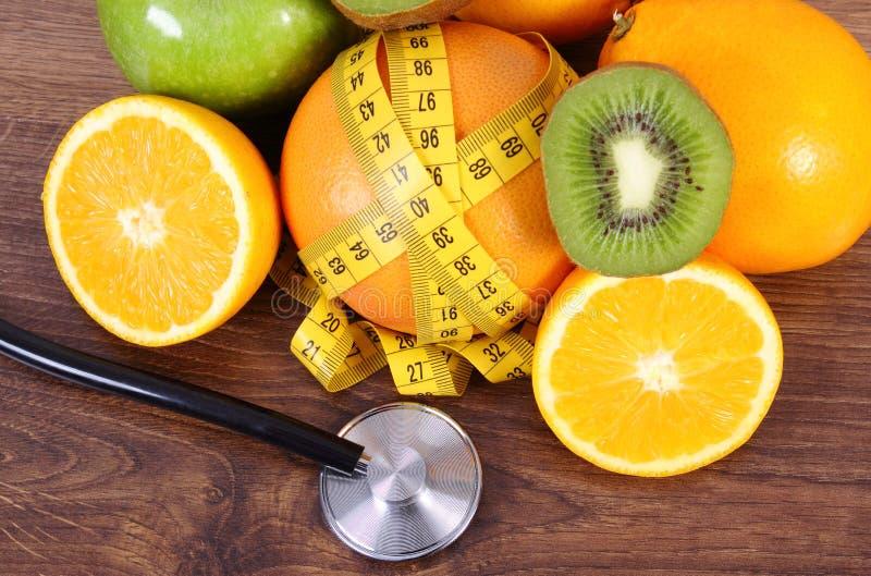 Stethoscoop, verse vruchten en centimeter, gezonde levensstijlen en voeding stock afbeeldingen