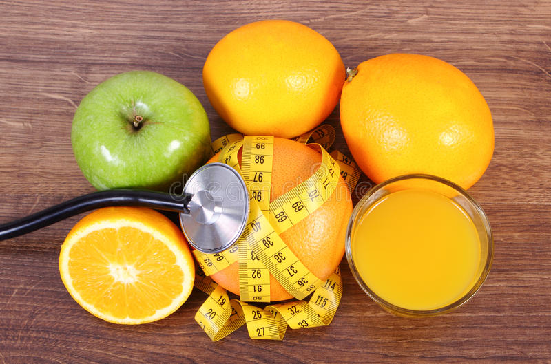 Stethoscoop, verse vruchten, sap en centimeter, gezonde levensstijlen en voeding stock fotografie