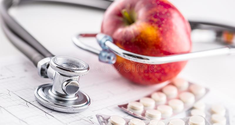 Stethoscope apple and pills on white background stock photography