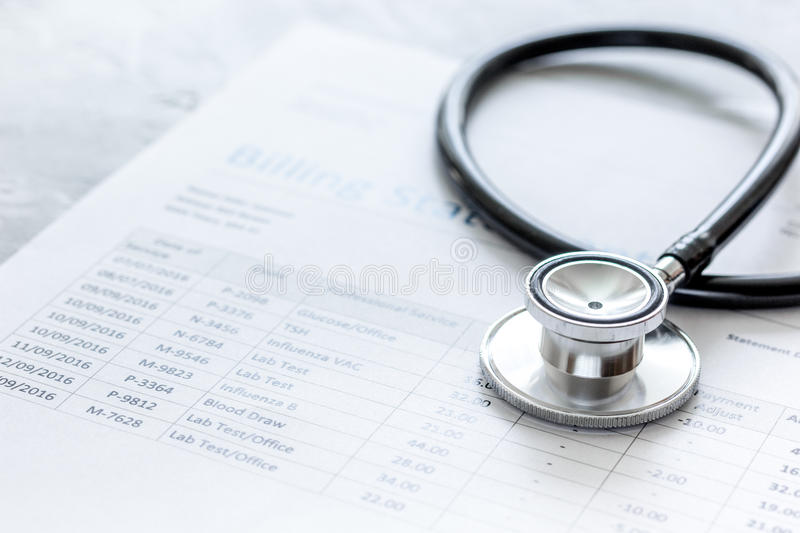 Stethoscope, billing statement for doctor`s work in medical center stone background royalty free stock photo