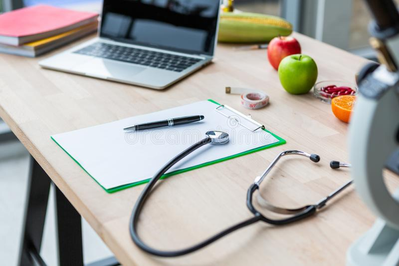 Stethoscope and blank note paper with labtop on nutritionist doctor table in laboratory room stock photo