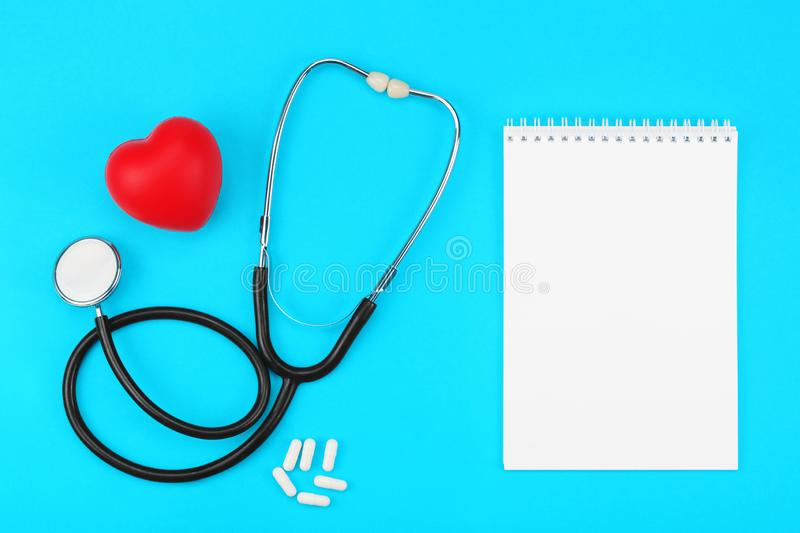 Stethoscope with blank notepad, red heart and white capsules on a blue background. royalty free stock photo