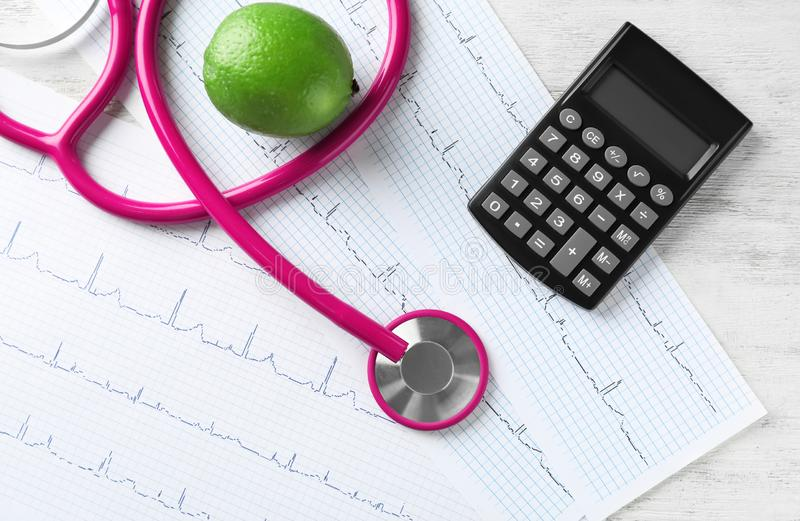 Stethoscope with calculator and cardiograms on wooden background. Health care concept royalty free stock photo