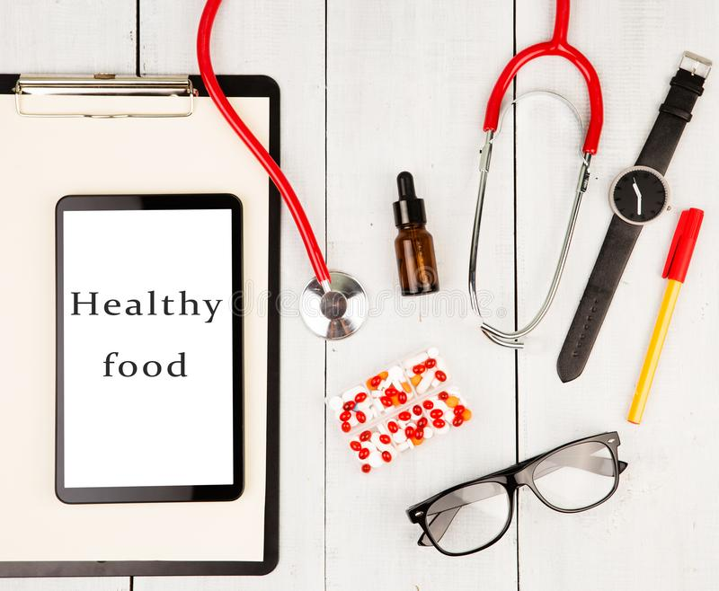 Stethoscope, clipboard, smartphone with text & x22;Healthy food& x22;, glasses, watch and pills stock photography