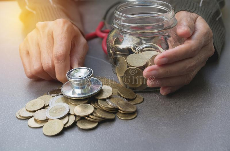Stethoscope with Coins in jar with money stack, Concept finance, accounting, business and saving investment. stock photos