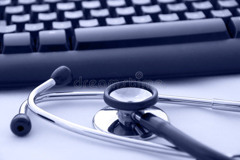 Stethoscope by a computer keyboard. A stethoscope by a computer keyboard. In blue light royalty free stock photo
