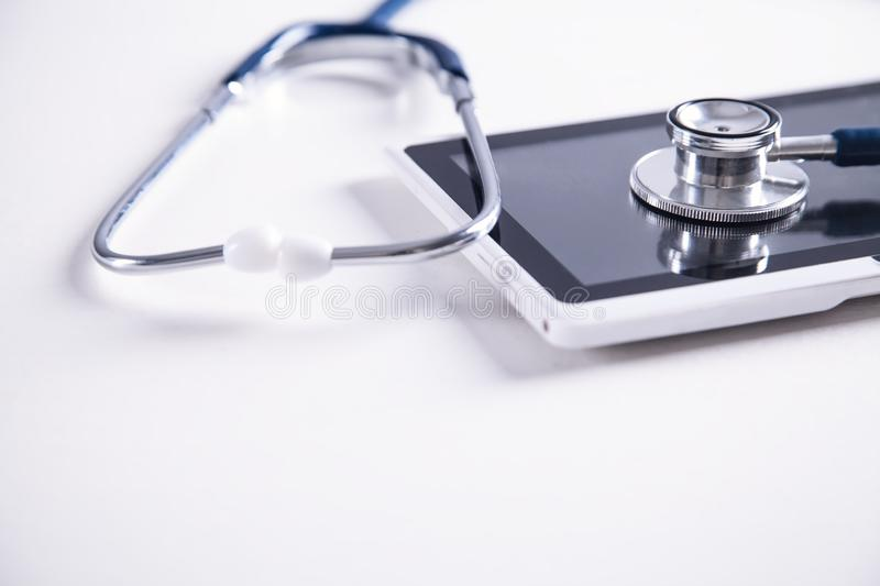 Stethoscope with digital tablet on white desk. Medical equipment. Space for your text stock image