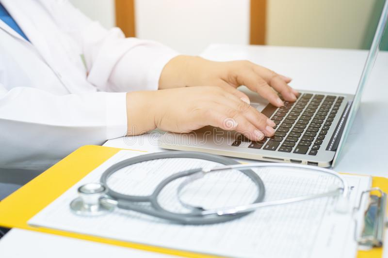 Stethoscope and Doctor working an Laptop on desk in hospital. Stethoscope on prescription clipboard andDoctor working an Laptop on desk in hospital stock photos
