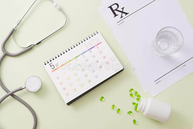 Stethoscope with drugs and pills on calendar page royalty free stock image