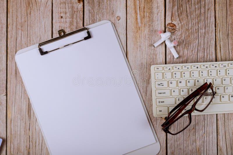 Stethoscope e caderno de papel no teclado sobre uma mesa de madeira imagens de stock