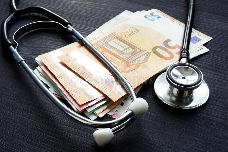 Stethoscope and euro banknotes on a desk. Health insurance and cost of medicine. royalty free stock photos