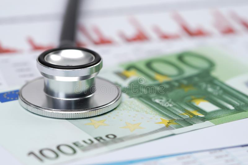Stethoscope on Euro banknotes and graph paper, stock image