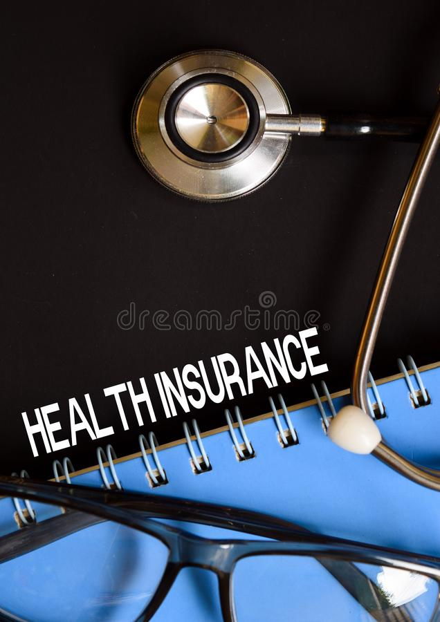 HEALTH INSURANCE word medical on top of black background stock photos