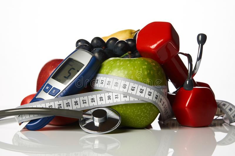 Stethoscope glucometer fruits and dumbbells, Diabetes concept royalty free stock photography