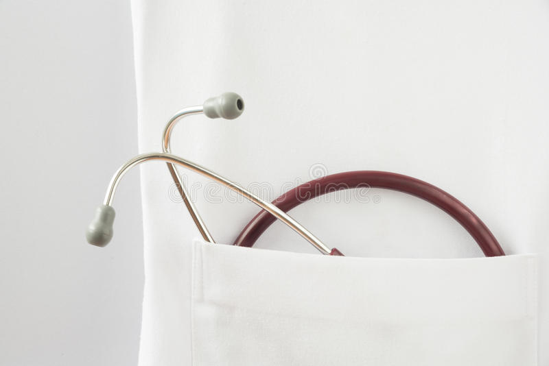 Stethoscope in the gown. A red stethoscope in the pocket of doctor gown on the white background royalty free stock photos