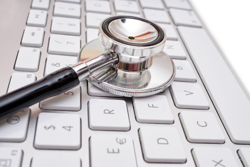 Stethoscope head on computer keyboard stock photo