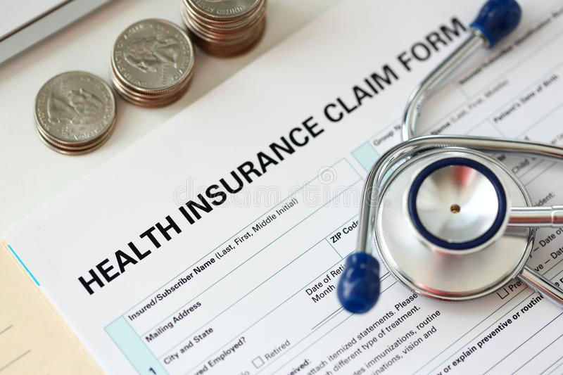 Stethoscope head metal quarter coins and silver pen lying on application form. At insurance agent worktable in company office closeup stock images