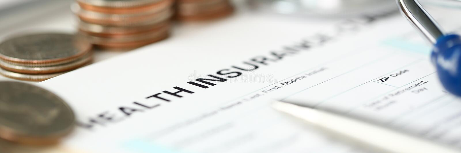 Stethoscope head metal quarter coins and silver pen lying on application form. At insurance agent worktable in company office closeup stock photos
