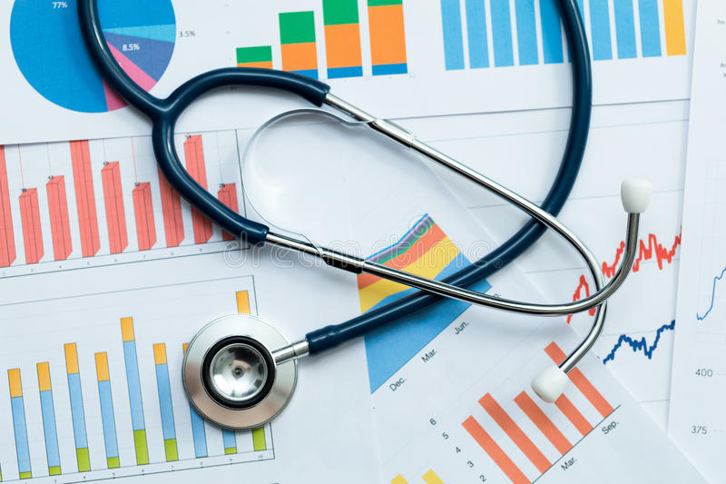 Stethoscope on healthcare stats and financial analysis charts royalty free stock photo