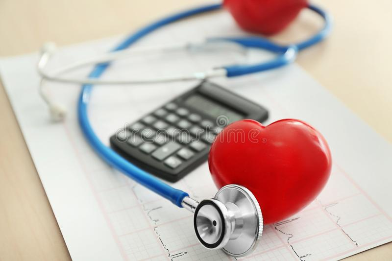 Stethoscope with heart, calculator and cardiogram on table stock photography