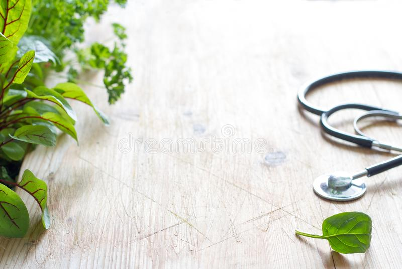 Stethoscope and herbs healthy life style and alternative medicine background concept. On wooden table stock photos