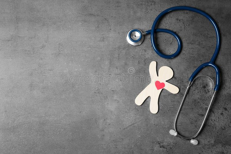 Stethoscope with human figure and heart on grey, flat lay. Space for text. Stethoscope with human figure and heart on grey background, flat lay. Space for text royalty free stock images