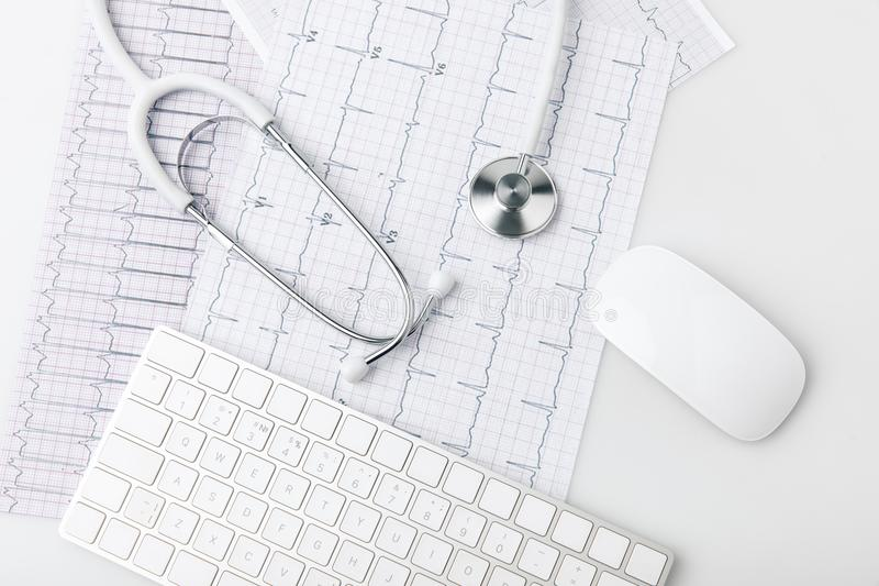 Stethoscope, keyboard and computer mouse laying on paper with cardiogram stock photography