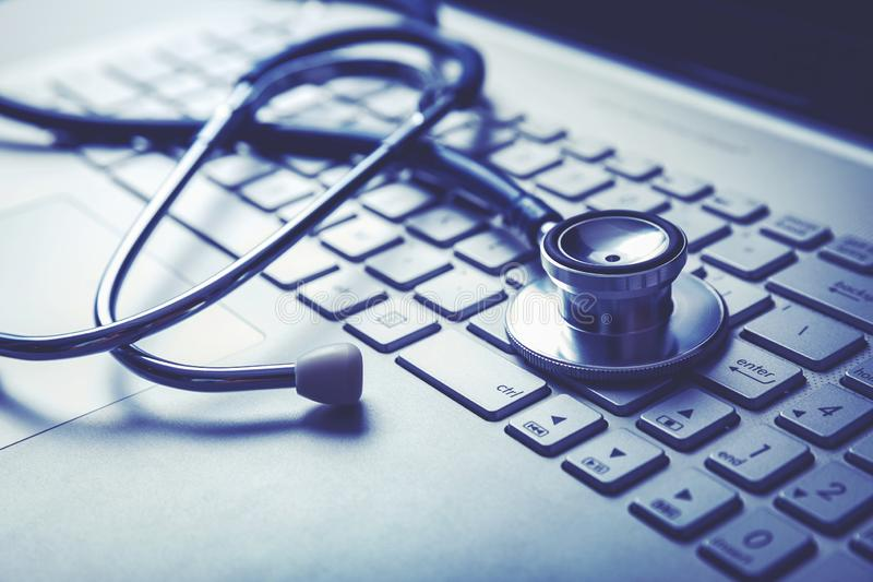 Stethoscope on laptop keyboard. computer diagnostics or e-health concept stock images