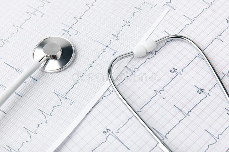 Stethoscope laying on paper with cardiogram royalty free stock images