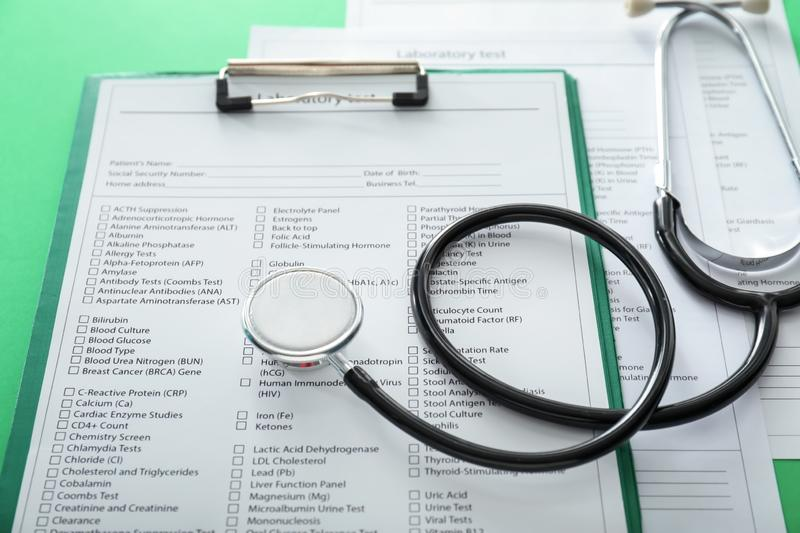 Stethoscope with lists of laboratory tests on color background. Health concept royalty free stock photography