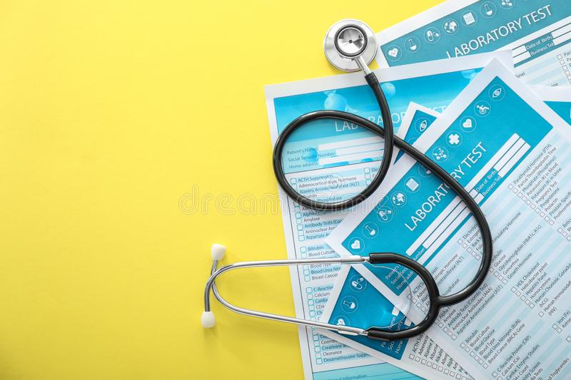 Stethoscope with lists of laboratory tests on color background. Health concept stock photo