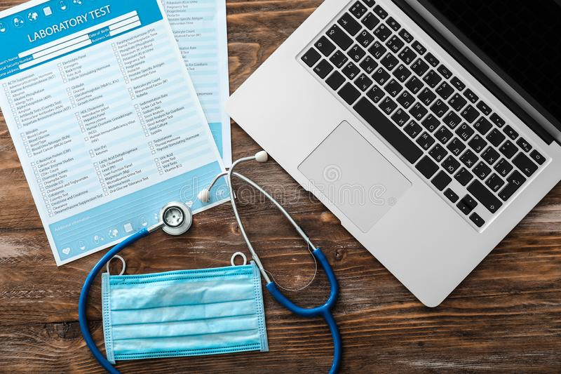 Stethoscope with lists of laboratory tests and laptop on wooden table. Health concept stock image