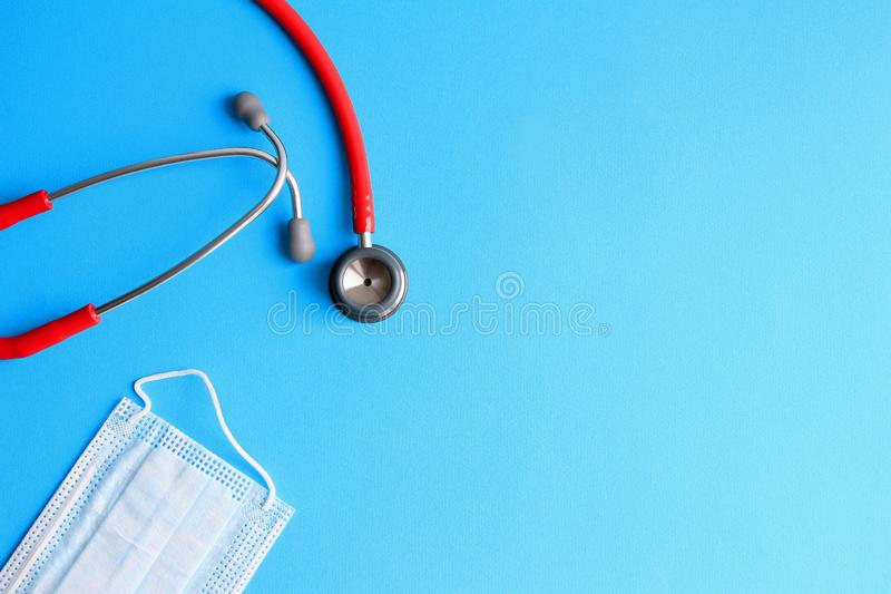 Stethoscope and medical mask on a blue background royalty free stock photos