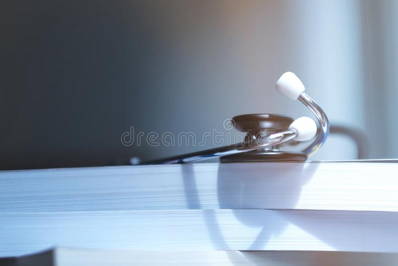 Stethoscope on medical textbooks in library stock images