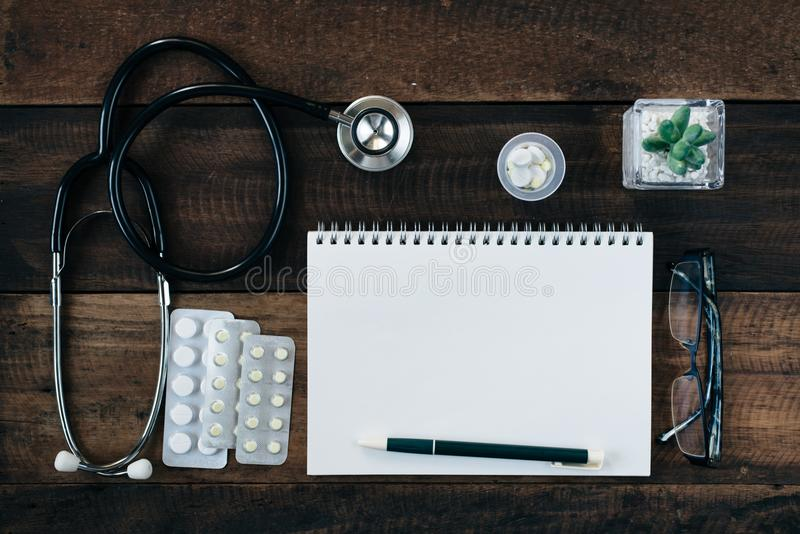 Stethoscope, medicine and notebook on wooden table background stock images