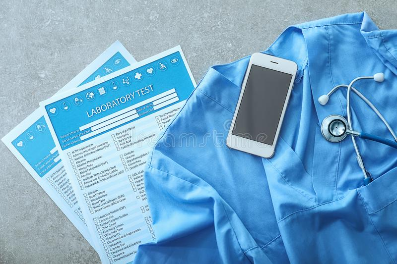 Stethoscope with mobile phone, doctor\'s uniform and lists of laboratory tests on grey table. Health concept stock photo