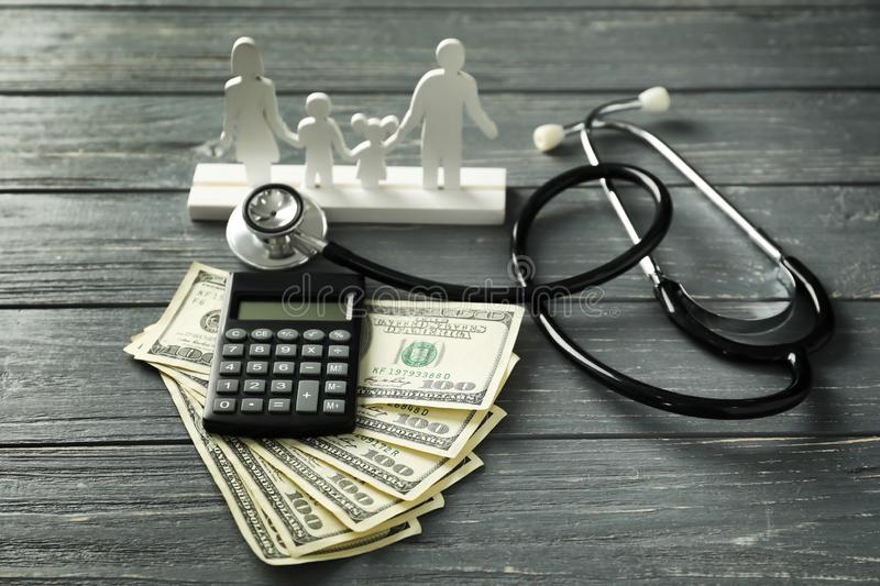 Stethoscope with money, calculator and family figure on wooden background. Health care concept stock images
