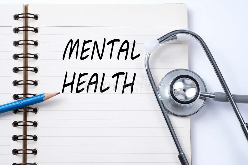 Stethoscope on notebook and pencil with MENTAL HEALTH words as m stock photo