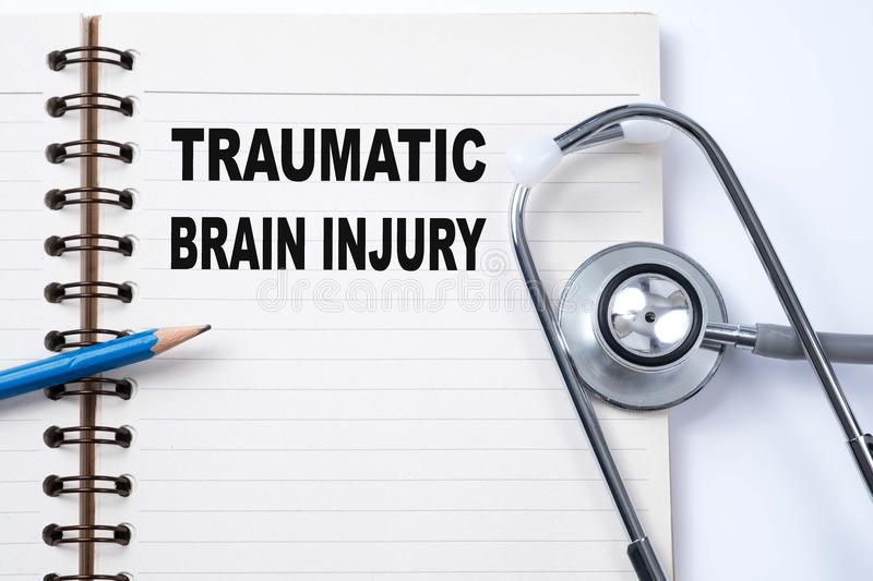 Stethoscope on notebook and pencil with Traumatic Brain Injury royalty free stock photography