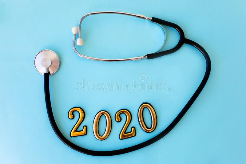 Stethoscope with 2020 number on blue background. Happy New Year for health care and medical banner/calendar cover stock photography