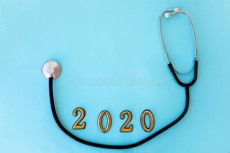 Stethoscope with 2020 number on blue background. Happy New Year for health care and medical calendar cover stock photo