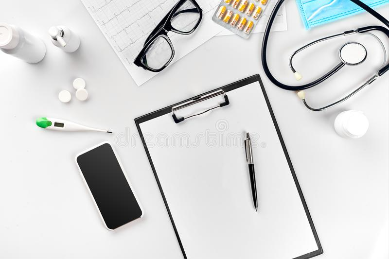 Stethoscope in the office of doctors.Top view of doctor`s desk table, blank paper on clipboard with pen. Copy space stock image