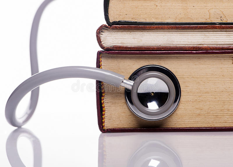 Stethoscope on old book. Close up stethoscope on old book on white background stock image