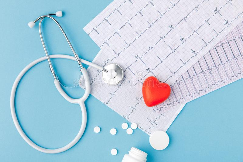 Stethoscope, paper with cardiogram, scattered pills and red heart stock photo