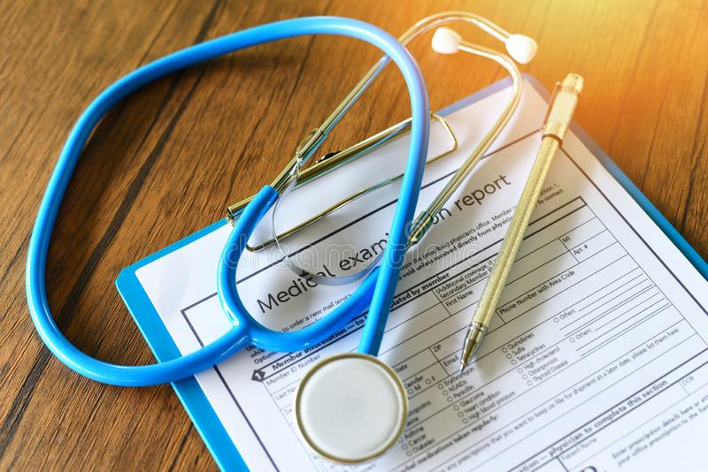 Stethoscope and pen on medical record - medical examination report on wooden table in the hospital - Health checks concept royalty free stock photo
