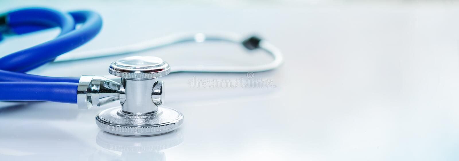 Stethoscope or phonendoscope on a doctor`s white desk. Treatment of cold or flu, banner size. Stethoscope or phonendoscope on a doctor`s white desk, for stock photo
