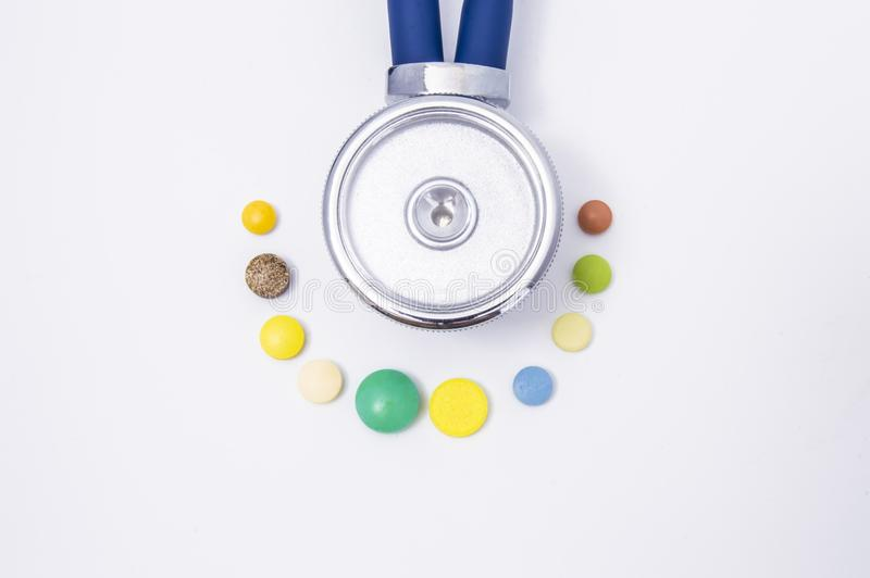 A stethoscope or phonendoscope is surrounded by medication - colorful medicine pills or tablets view from above. The treatment of stock photo