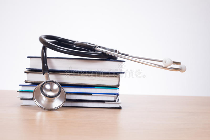 Stethoscope on pile of journals. Acoustic stethoscope on pile of planners lying on desk stock image