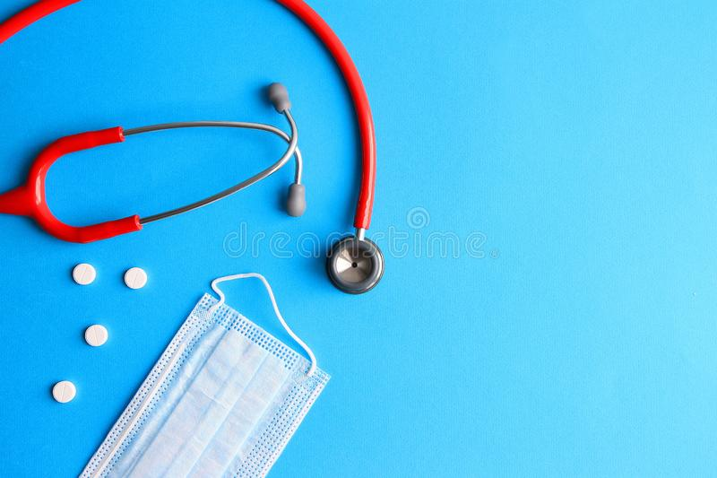Stethoscope, pills and medical mask on a blue background royalty free stock photos